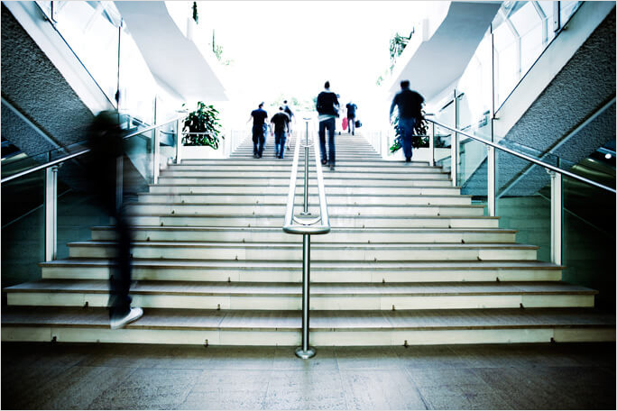 People walking up steps in a modern building